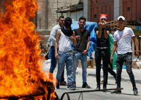 فلسطينيون في 24 يونيو 2019 قرب مدينة الخليل في الضفة الغربية قرب إطار مشتعل خلال احتجاجات على ورشة العمل الأميركية