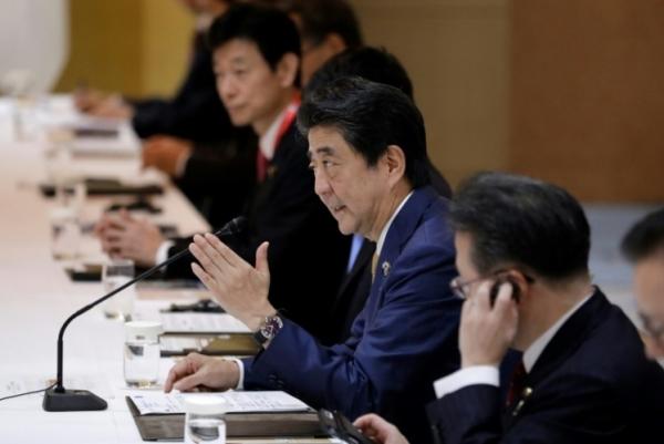 رئيس الوزراء الياباني شينزو آبي (وسط) خلال لقاء ثنائي مع رئيس الوزراء الهندي ناريندرا مودي في 27 يونيو 2019 عشية قمة مجموعة العشرين في أوساكا باليابان