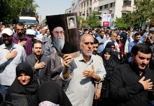 ايرانيون يرفعون صورة خامنئي خلال مسيرة احتجاجية