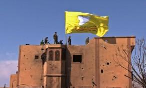 صورة وزعتها قناة روناهي التلفزيونية الكردية من لقطة فيديو تظهر فيها راية قوات سوريا الديموقراطية الصفراء مرفوعة فوق مبنى في الباغوز، آخر معاقل تنظيم الدولة الإسلامية الذي سقط في 23 آذار/مارس 2019 مع إعلان