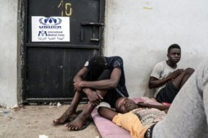 مهاجرون غير شرعيين يجلسون في مركز احتجاز في الزاوية على بعد 45 كلم غرب العاصمة طرابلس