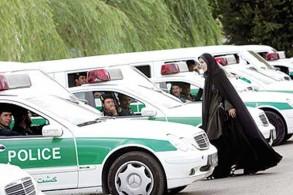 شرطية إيرانية تمر أمام سيارات للشرطة في طهران (أ.ف.ب)