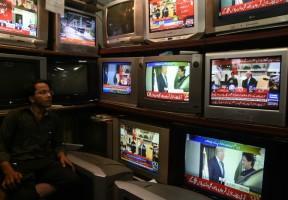 تاجر باكستاني يتابع اجتماع الرئيس الأميركي دونالد ترمب ورئيس وزراء باكستان عمران خان، في محله في كراتشي الأحد 22 تموز/يوليو 2019