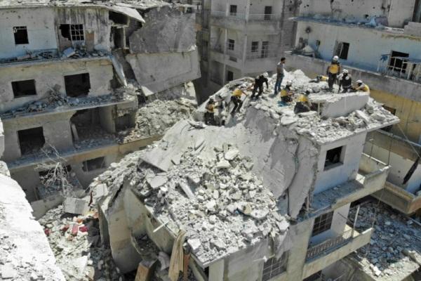 مسعفون من الخوذ البيضاء يبحثون عن ضحايا في ركام مبنى تعرض لغارة في مدينة أريحا في شمال غرب سوريا في 27 يوليو 2019