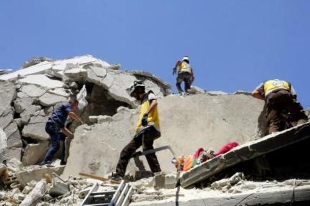 عناصر من الخوذ البيضاء يبحثون بين ركام مبنى اثر غارة جوية في اريحا في محافظة ادلب