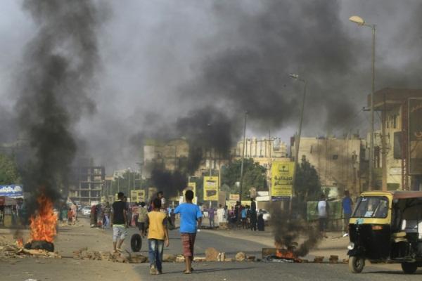 متظاهرون يحرقون إطارات السيارات في وسط شارع رئيسي في الخرطوم في 27 يوليو 2019 احتجاجا على نتائج التحقيق في فض اعتصام الخرطوم في يونيو
