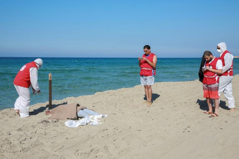 عناصر من الهلال الاحمر الليبي قرب جثة احد المهاجرين على شاطئ الخمس شرق طرابلس الجعة في 26 تموز/يوليو 2019