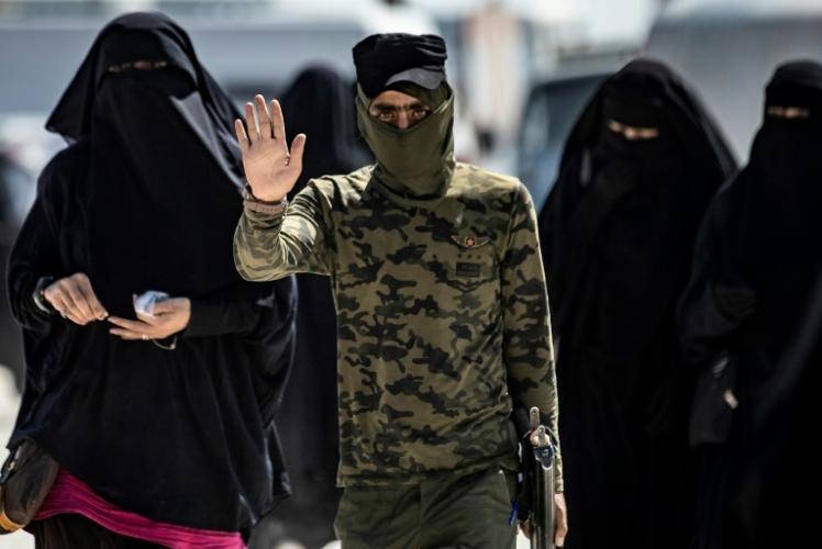 قوات أمنية ترافق نساء يعتقد انهن زوجات مقاتلي تنظيم داعش في مخيم الهول في محافظة الحسكة في شمال شرق سوريا