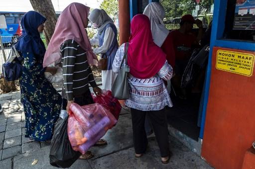 مواطنة أندونيسية تحمل عبوات بلاستيكية لاستبدالها بتذكرة سفر بالحافلة