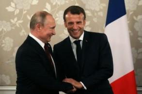 الرئيس الفرنسي ماكرون يصافح نظيره الروسي بوتين خلال لقائهما على هامش قمة مجموعة العشرين في اوساكا