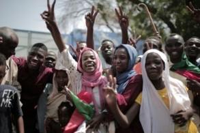 سودانيات يحتفلن أمام قاعة الصداقة حيث كان يجري تشكيل مجلس حاكم جديد غالبيته من المدنيين وسط الخرطوم
