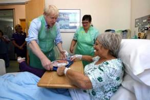 جونسون يقدم الطعام إلى مريضة خلال زيارته مستشفى في توركواي في جنوب غرب بريطانيا بتاريخ 23 أغسطس 2019