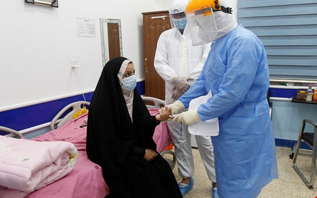 طبيب يفحص عراقية من اصابة بفايروس كورونا
