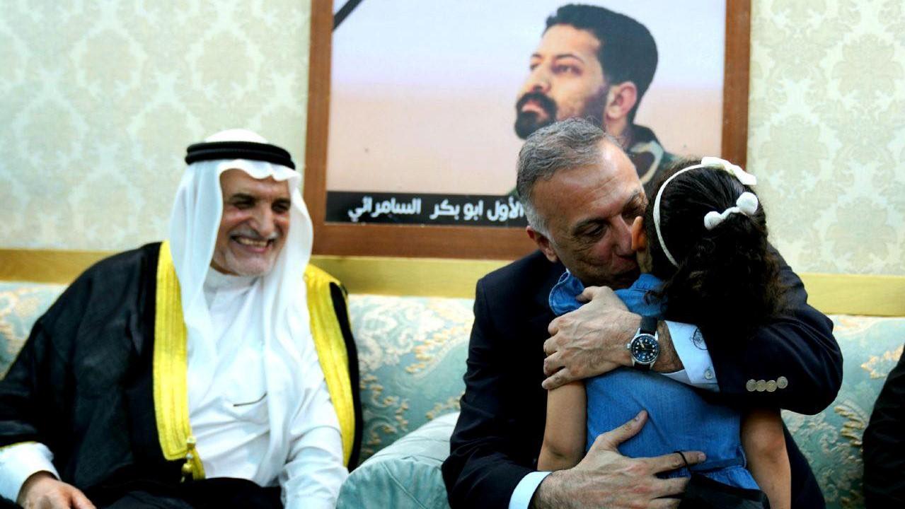 الكاظمي محتضنا ابنة ضابط عراقي اعدمه داعش