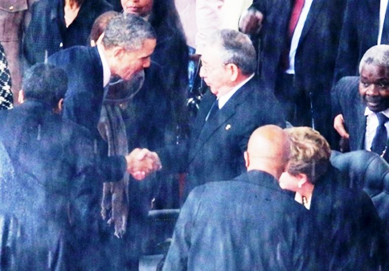 أوباما مصافحًا كاسترو على هامش تأبين نلسون مانديلا في جنوب افريقيا