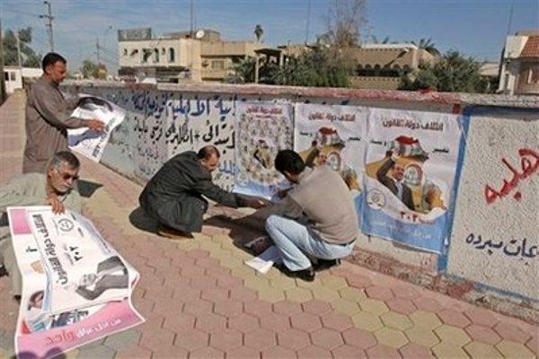 عراقيون يعلقون ملصقات إنتخابية في بغداد