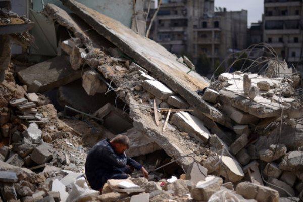 سوري يجلس أمام منزل مدمر في سوريا