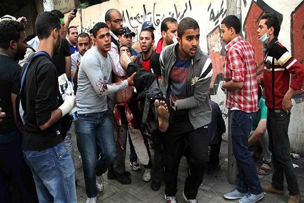 شباب مصريون يحملون جريحاً في المواجهات بين قوات الامن والاخوان
