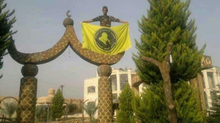 مقاتل عراقي في سوريا يرفع علم تنظيمه