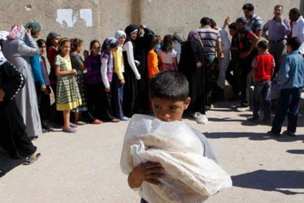 لاجئون سوريون في طابور لتلقي المساعدات الشحيحة