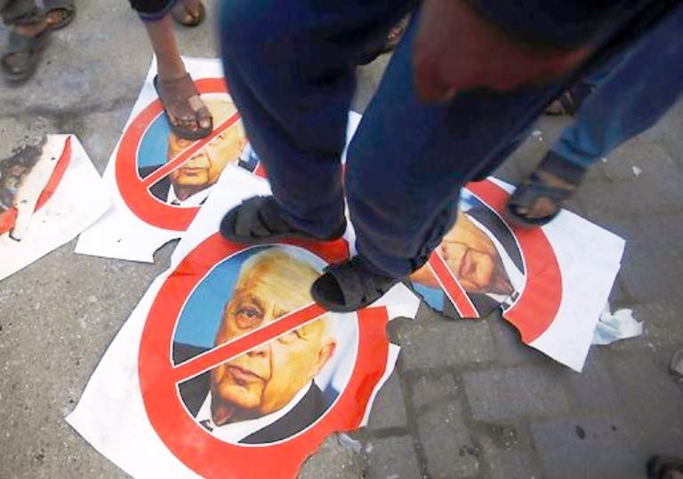 فلسطينيون يدوسون على صور شارون ابتهاجا بموته