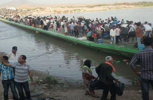 لاجئون سوريون يعبرون جسر فيشخابور إلى اقليم كردستان العراق