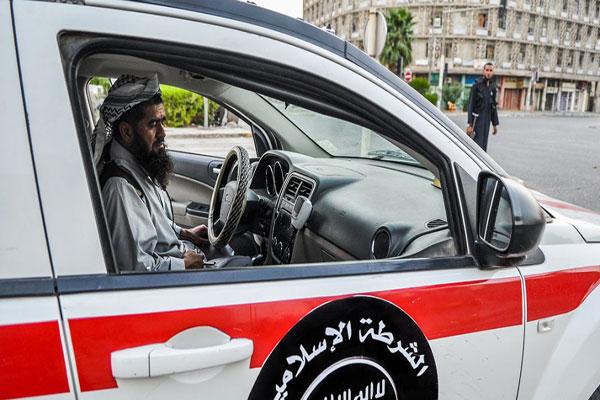 أحد عناصر الشرطة الإسلامية التاتابعة لداعش يقود إحدى سيارات الشرطة في الموصل