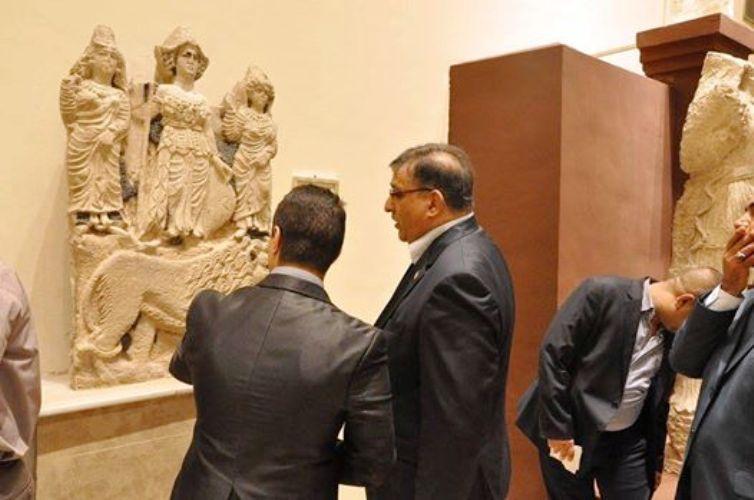 صورة لوزير السياحة والاثار العراقي لواء سميسم بالقرب من قطع اثرية محفوظة في متحف.