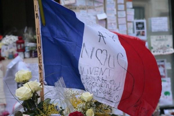 أزهار وعلم فرنسي أمام مقر صحيفة شارلي إيبدو