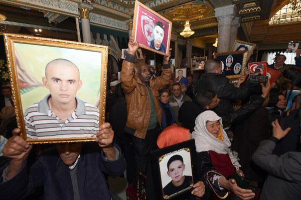 أسر ضحايا الثورة يرفعون صور أبنائهم
