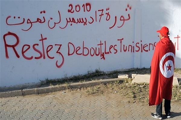 تونسي لف نفسه بعلم بلاده يتأمل في شعارات جدارية على جانب جادة محمد البوعزيزي في مدينة سيدي بوزيد