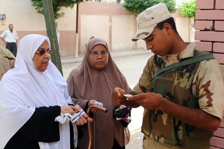 جندي مصري يدقق بهويتي إمرأتين قبيل الادلاء بصوتيهما