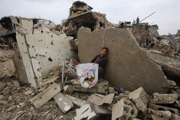 فتى سوري فوق ركام منزله في حلب