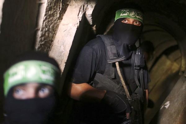 عنصران من كتائب القسام الجناح العسكري لحماس داخل نفق يربط قطاع غزة بمصر