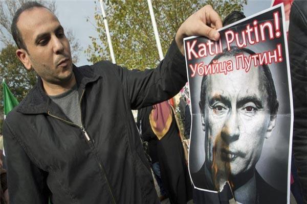 متظاهر يحرق صورة للرئيس الروسي كُتب عليها