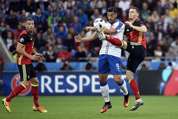 مدافع بلجيكا فيرمايلين يحاول قطع الكرة من اللاعب الإيطالي
