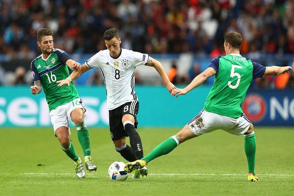 مسعود أوزيل يحاول الحفاظ على الكرة من لاعبي إيرلندا الشمالية