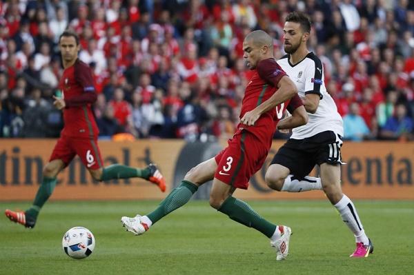 البرتغالي بيبي يصارع على الكرة مع النمساوي مارتن هارنيك