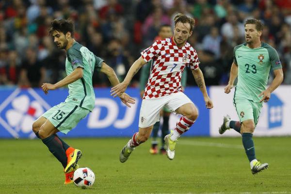 ينجم وسط كرواتيا راكيتيتش يحاول التخلص من لاعبي المنتخب البرتغال