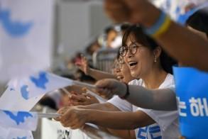 كوريون جنوبيون يلوحون بالعلم الموحد خلال متابعتهم منافسات في كرة الطاولة في مدينة دايجون الكورية الجنوبية