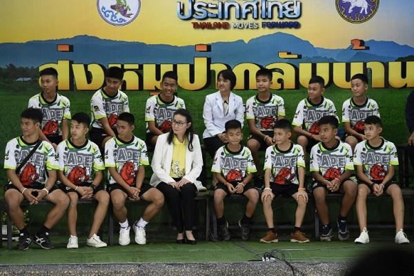 الفتيان التايلانديون الاثنا عشر ومدربهم لكرة القدم خلال مؤتمر صحافي بعد خروجهم من مستشفى شيانغ راي