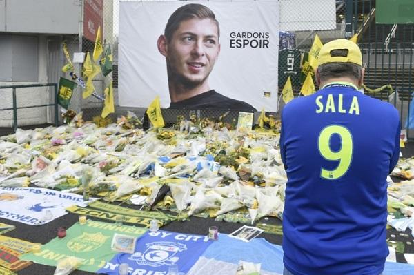 مشجع يرتدي قميص سالا أمام صورة له وباقات من الزهر خارج ملعب فريق نانت الفرنسي