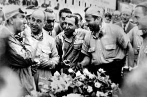 السائق الأرجنتي خوان مانويل فانجيو (الثاني من اليسار) يتحدث الى الإيطالي جيوسيبي فارينا على حلبة سبا فرانكورشان في 18 يونيو 1950.