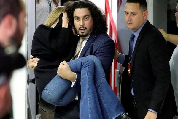 المحامي دانيلو غارسيا أندرادي يحمل عارضة الأزياء لحمايتها بعد خروجها من المحكمة