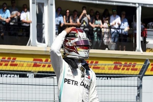 سائق مرسيدس البريطاني لويس هاميلتون يحيي الجماهير عقب انتزاعه المركز الأول في جولة التجارب الرسمية لجائزة فرنسا الكبرى في الفورمولا واحد
