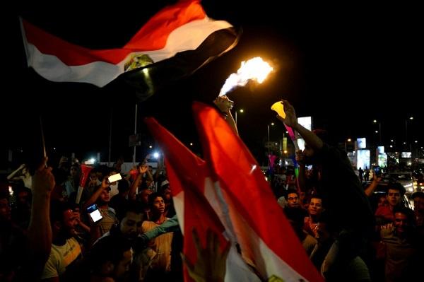 مصريون يحتفلون في شوارع القاهرة بفوز منتخب بلادهم على زيمبابوي في بطولة كأس الأمم الإفريقية في كرة القدم، في 21 حزيران/يونيو 2019.