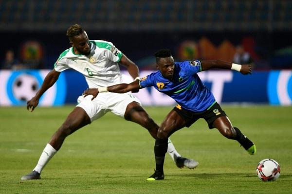 المدافع السنغالي ساليف سانيه (الى اليسار) يتنافس على الكرة مع التنزاني سيمون موسوفا
