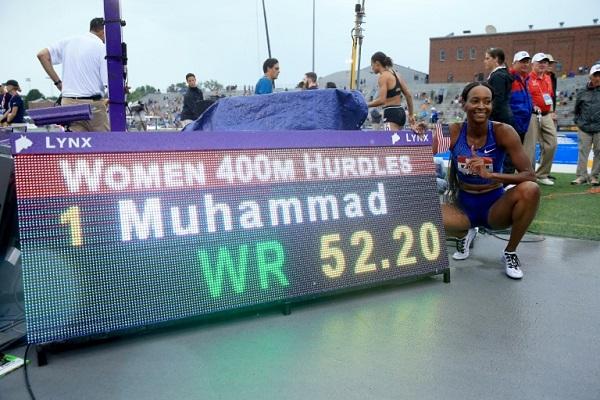 العداءة الاميركية دليلة محمد تلتقط صورة إلى جانب اللوحة الالكترونية التي تشير إلى رقمها القياسي العالمي في سباق 400 م حواجز والذي سجلته في بطولة الولايات المتحدة