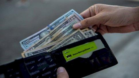 رجل يعرض محفظته بالدولار الأمريكي في أحد شوارع هافانا ، في 15 سبتمبر 2020. مع عودة الدولار إلى اقتصاد الجزيرة ، لا أحد يريد البيزو الكوبي القابل للتحويل (CUC)