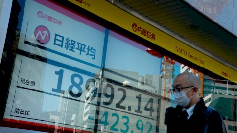رجل يسير قبل لوحة عرض أسعار البورصة في طوكيو في 12 آذار/مارس 2020